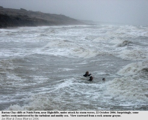 Storm waves eroding Barton Clay at Naish Farm near Highcliffe, with surfers undeterred by the wave conditions