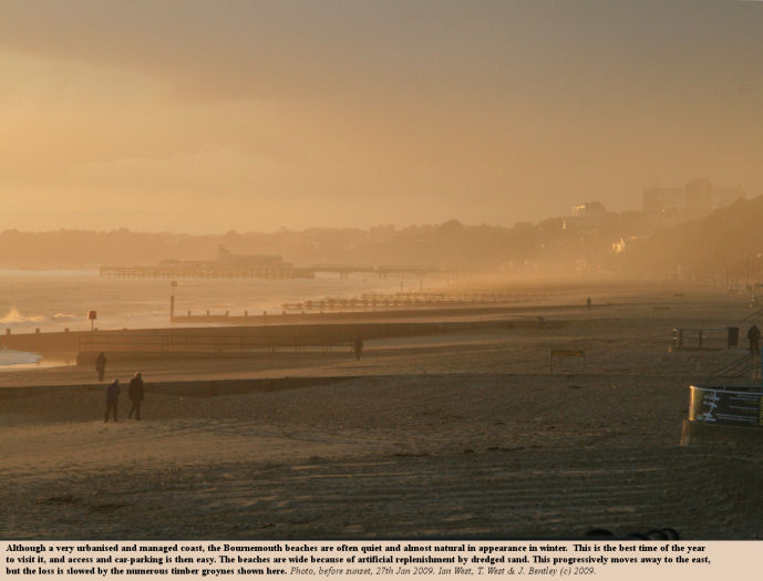 View of Bournemouth Pier from Boscombe Pier, late on a winter's day, showing wide sandy beaches and timber groynes