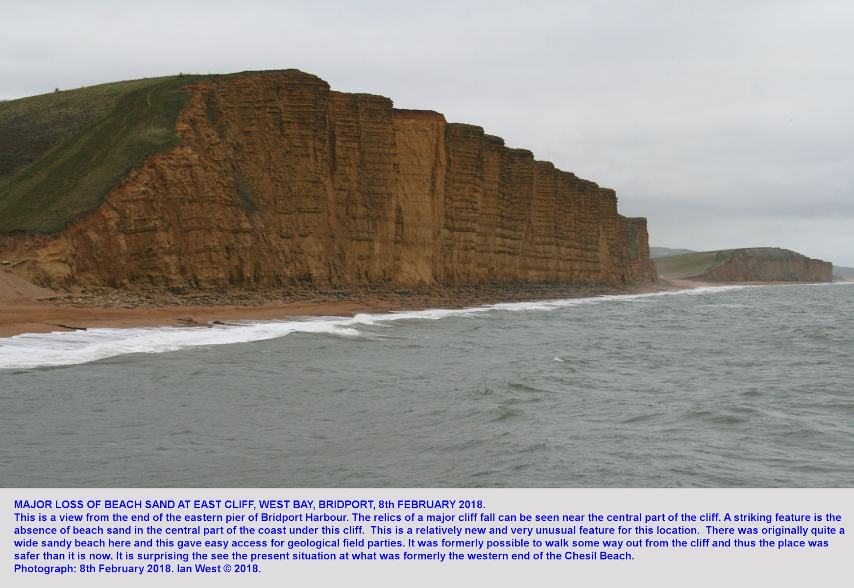 View from pier of East Cliff, West Bay, Bridport, Dorset, with an unusually  narrow and eroded beach adjacent to vertical cliffs of Bridport Sand Formation, 8th February, 2018