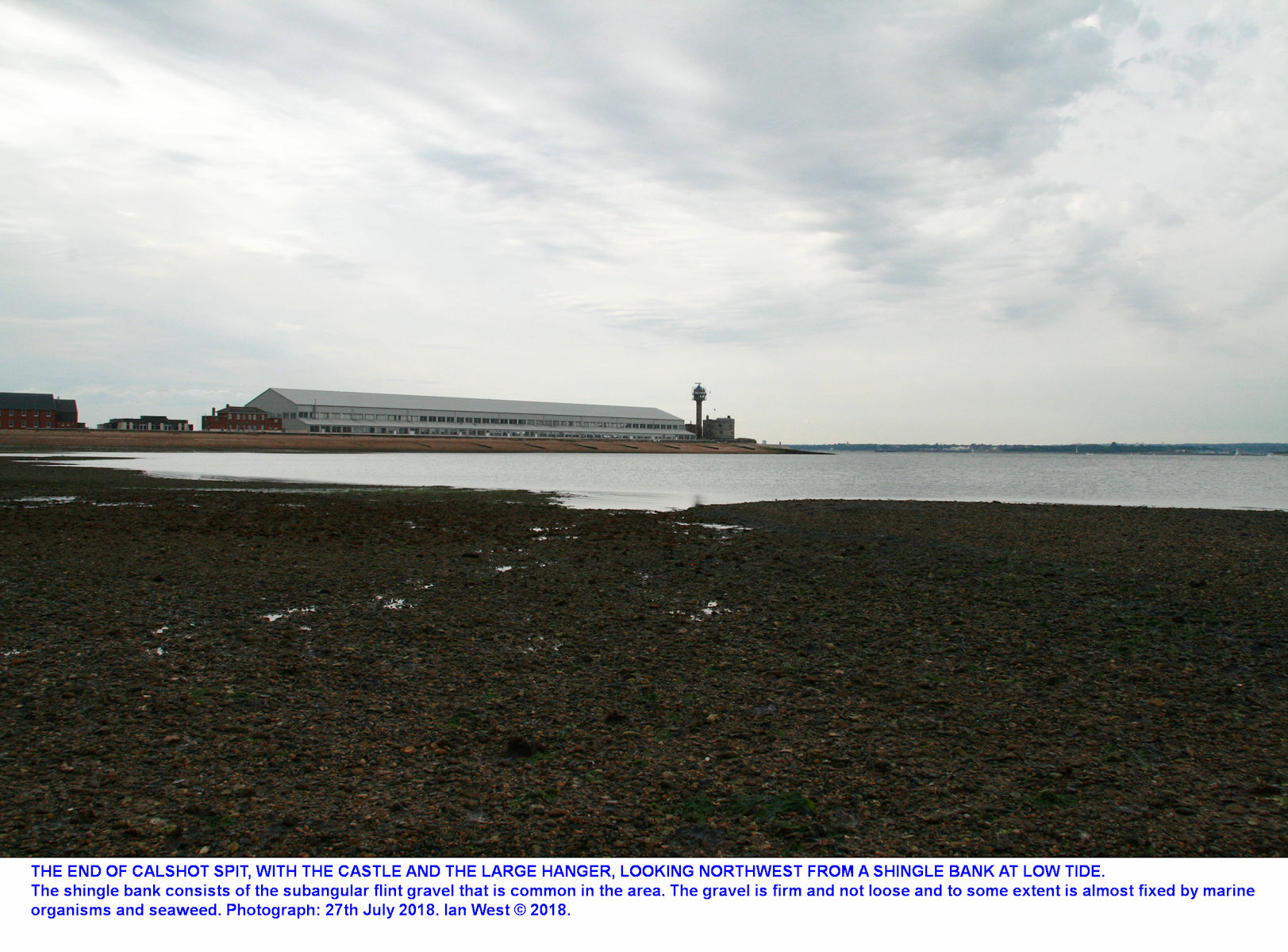 A view of the end of Calshot Spit with the castle and a larger, former, hanger, from a very low-tide, dark, gravel bank to the south, 2018