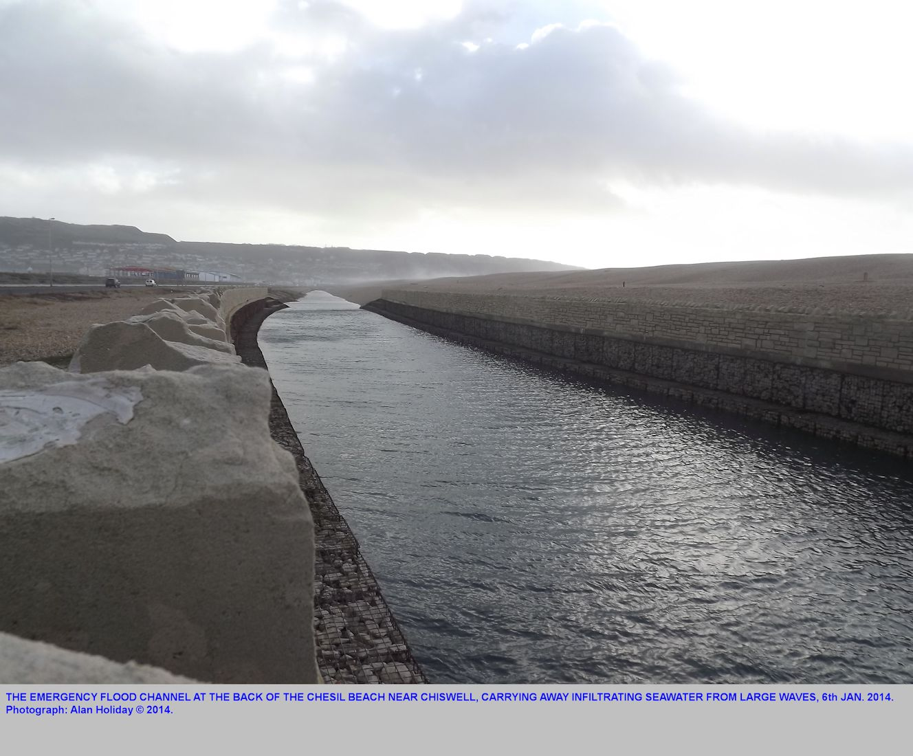The flood water channel at the back of Chesil Beach in action while large storm waves wash up the beach and supply infiltration water, 6th January 2014, photography by Alan Holiday