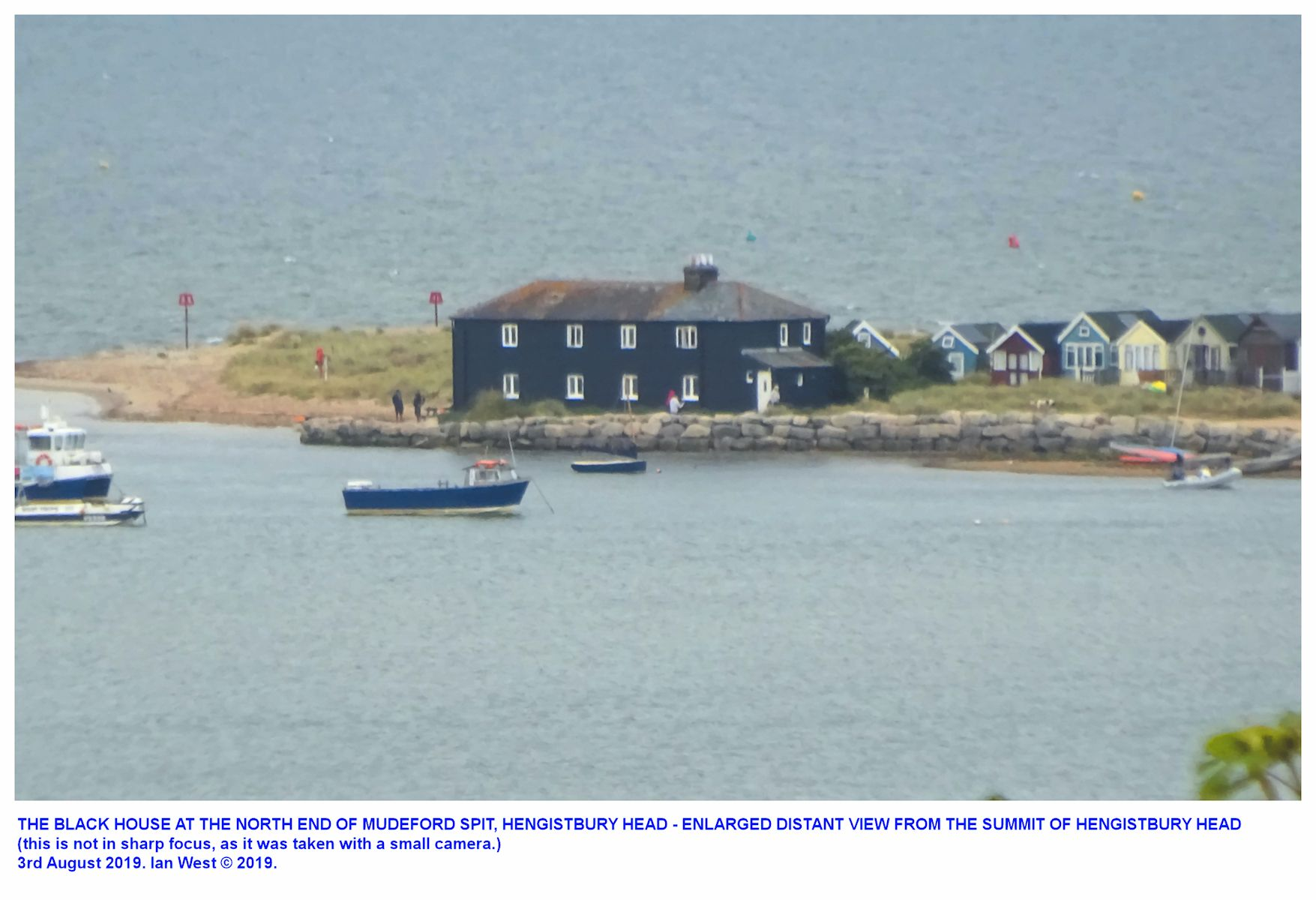The Black House, at the north end of Mudeford Spit, Hengistbury Head,  Dorset, seen with a zoom lens from the top of Warren Hill, 3rd August 2019