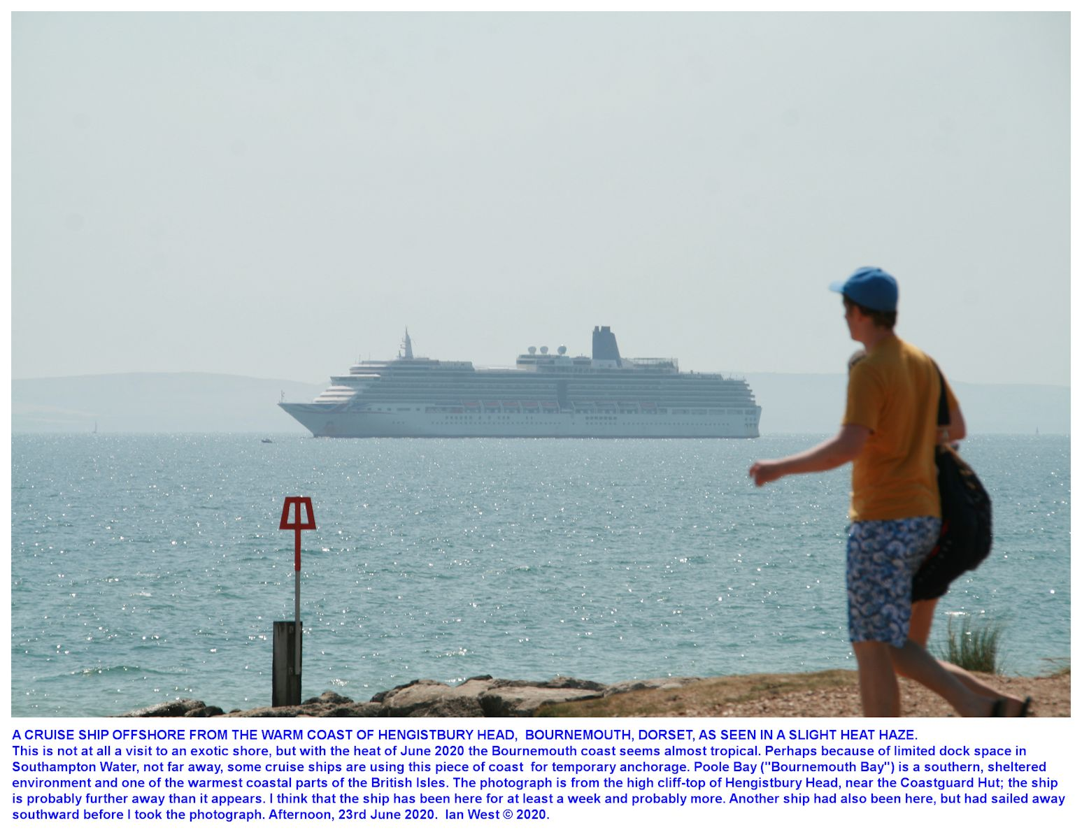 Seen from the cliff top of Hengistbury Head, near the old look-out hut, - offshore -  a cruise ship, not in use because of the pandemic in July 2020, and remaining idle and anchored in Poole Bay