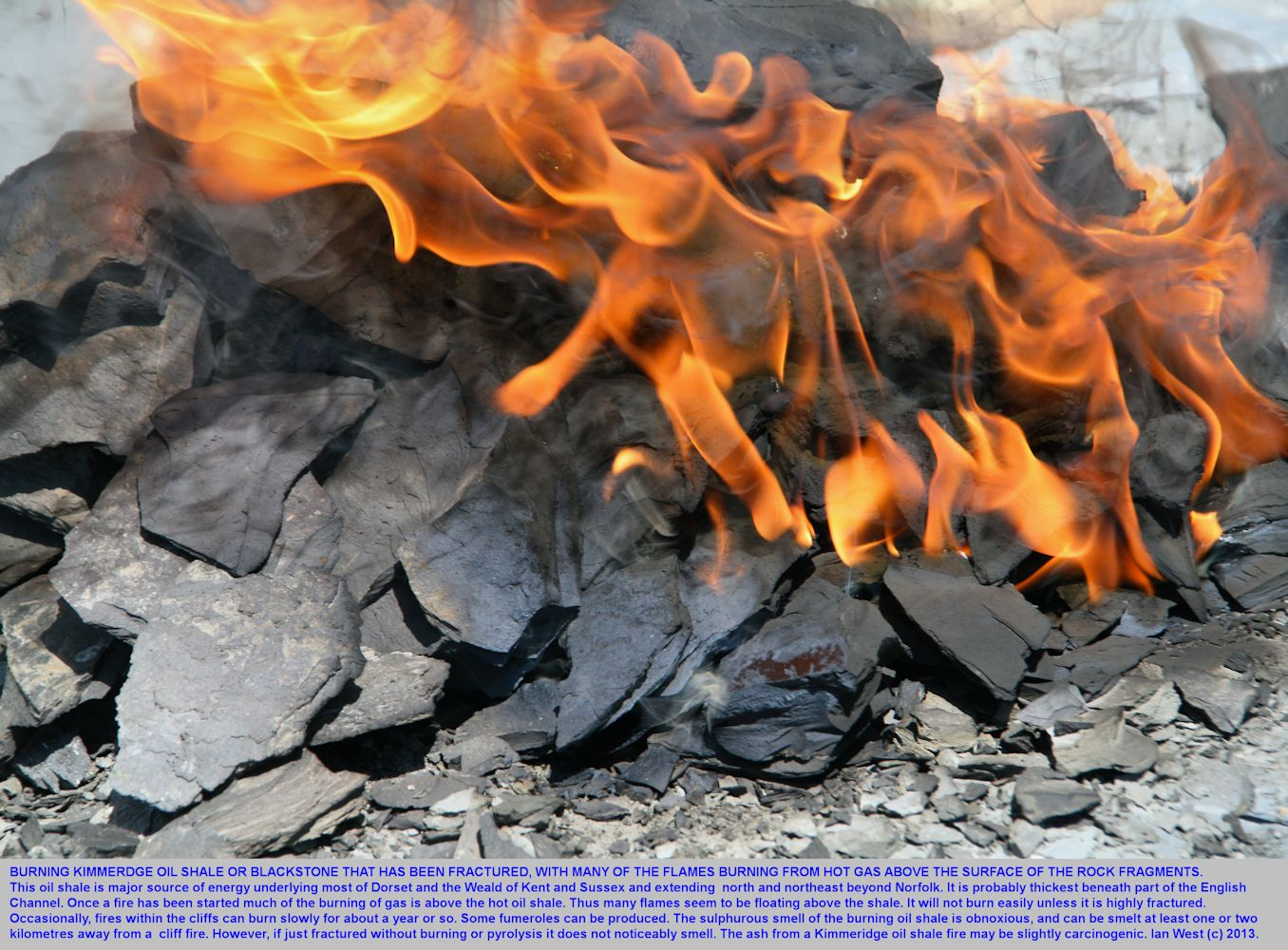 Tongue-like flames above artificially burning Kimmeridge oil shale or Blackstone, east of  Kimmeridge Bay, Dorset, 2013