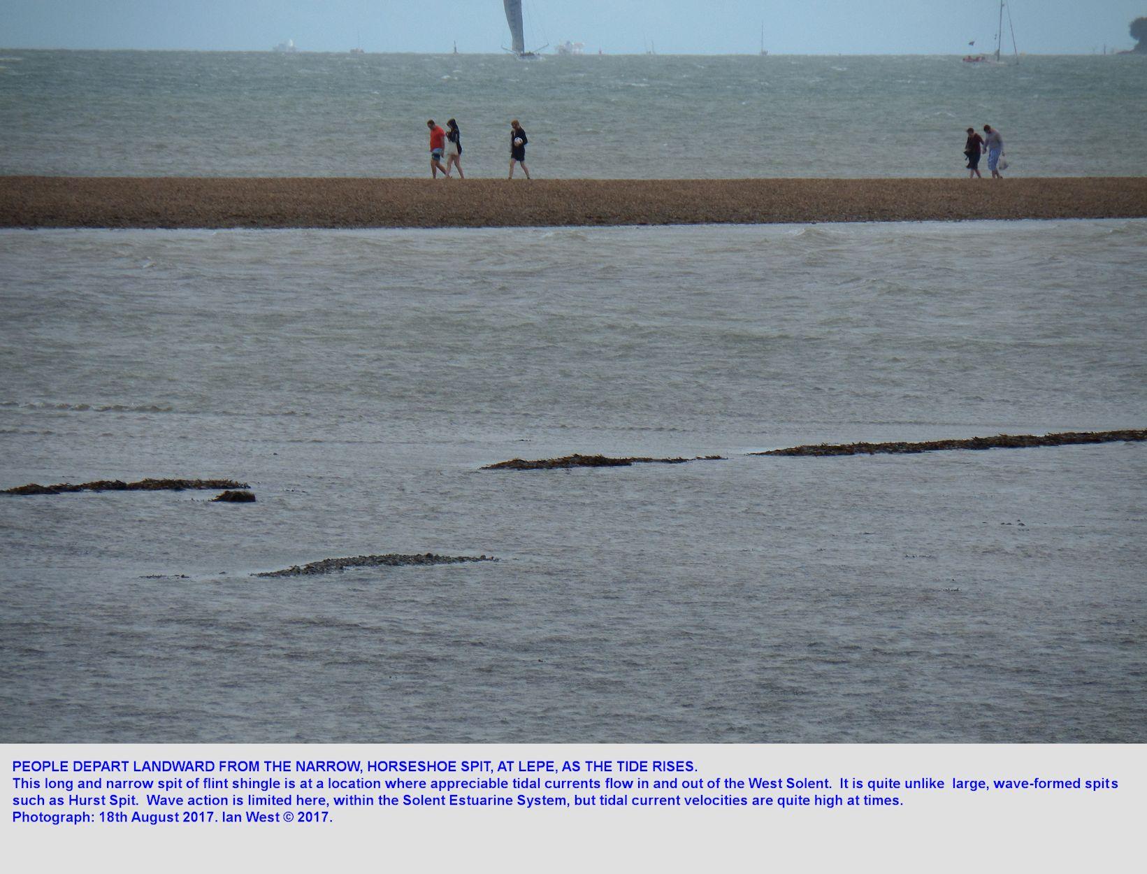 People leave Horse Spit, the transverse estuarine spit of shingle, east of Stone Point, Lepe, as the tide rises