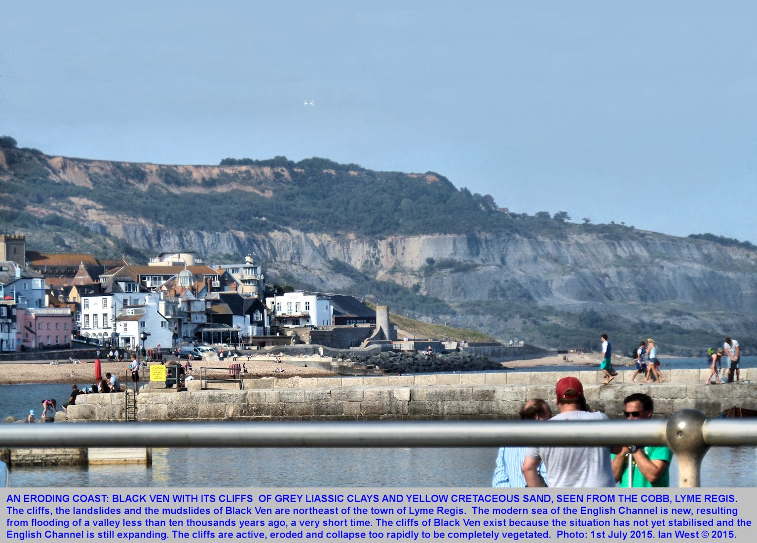 The eroding cliff of Black Ven seen from the Cobb and behind the town of Lyme Regis, Dorset, June 2015