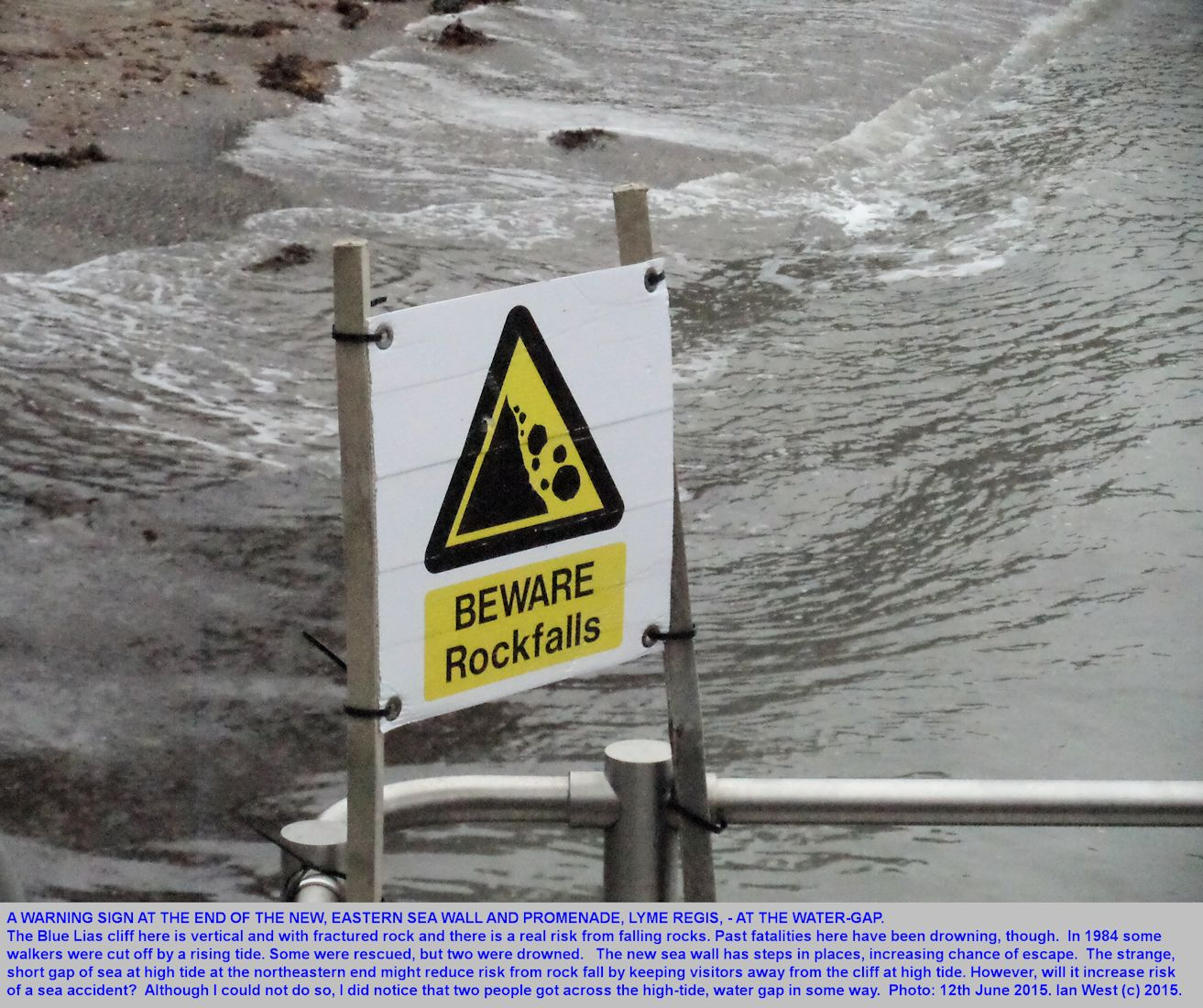 A warning sign about rock-fall near the vertical East Cliff of Blue Lias at the end of the new eastern sea wall and promenade, Lyme Regis, Dorset