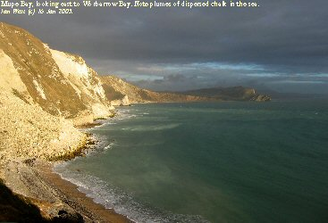 Chalk Cliffs of Mupe Bay, Dorset, with cliff falls and plumes of dispersed chalk in the sea