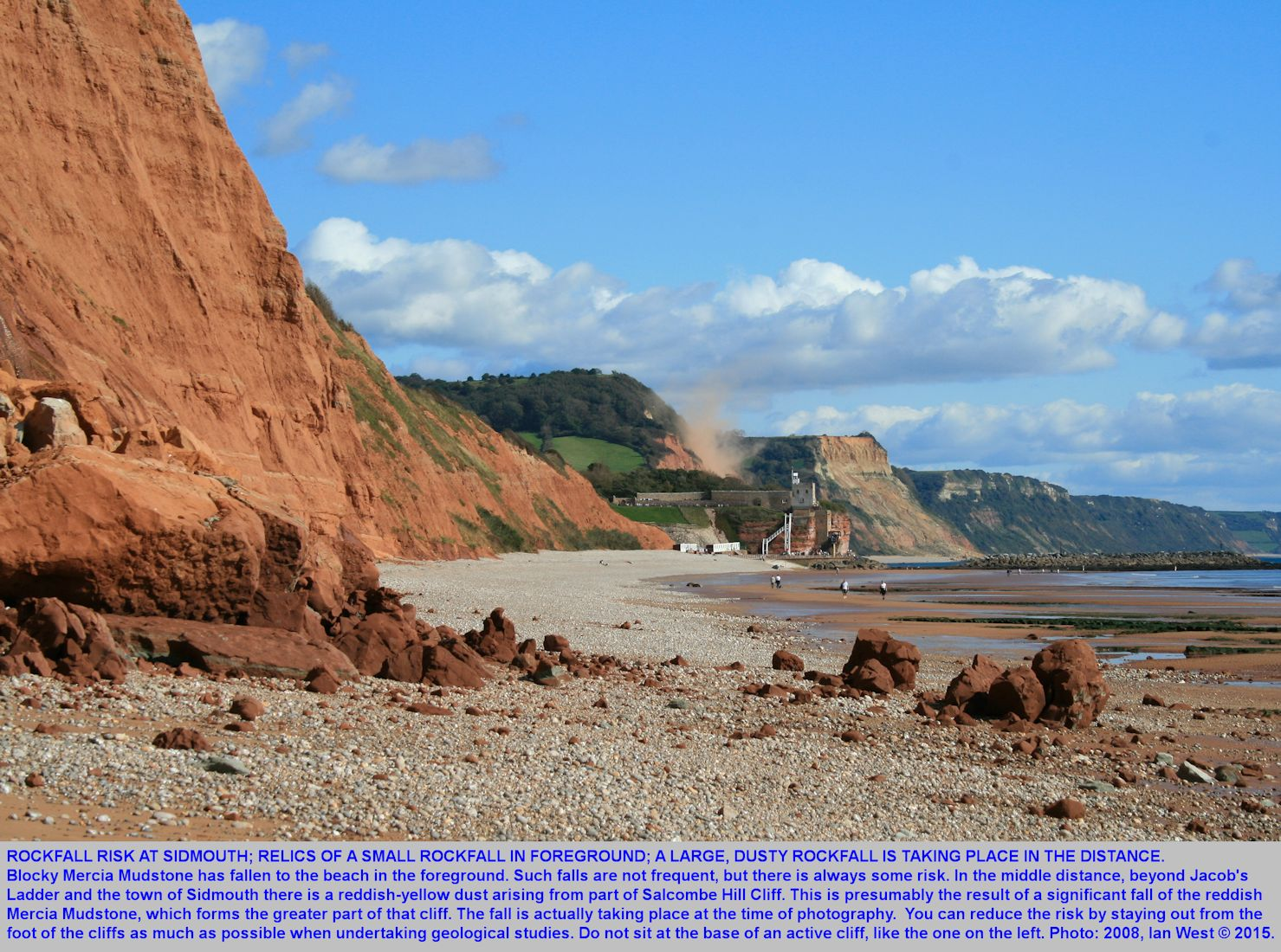 Sidmouth, Devon, rockfall hazard, with relics of an old rockfall in the foreground and an active rockfall in the distance, raising dust