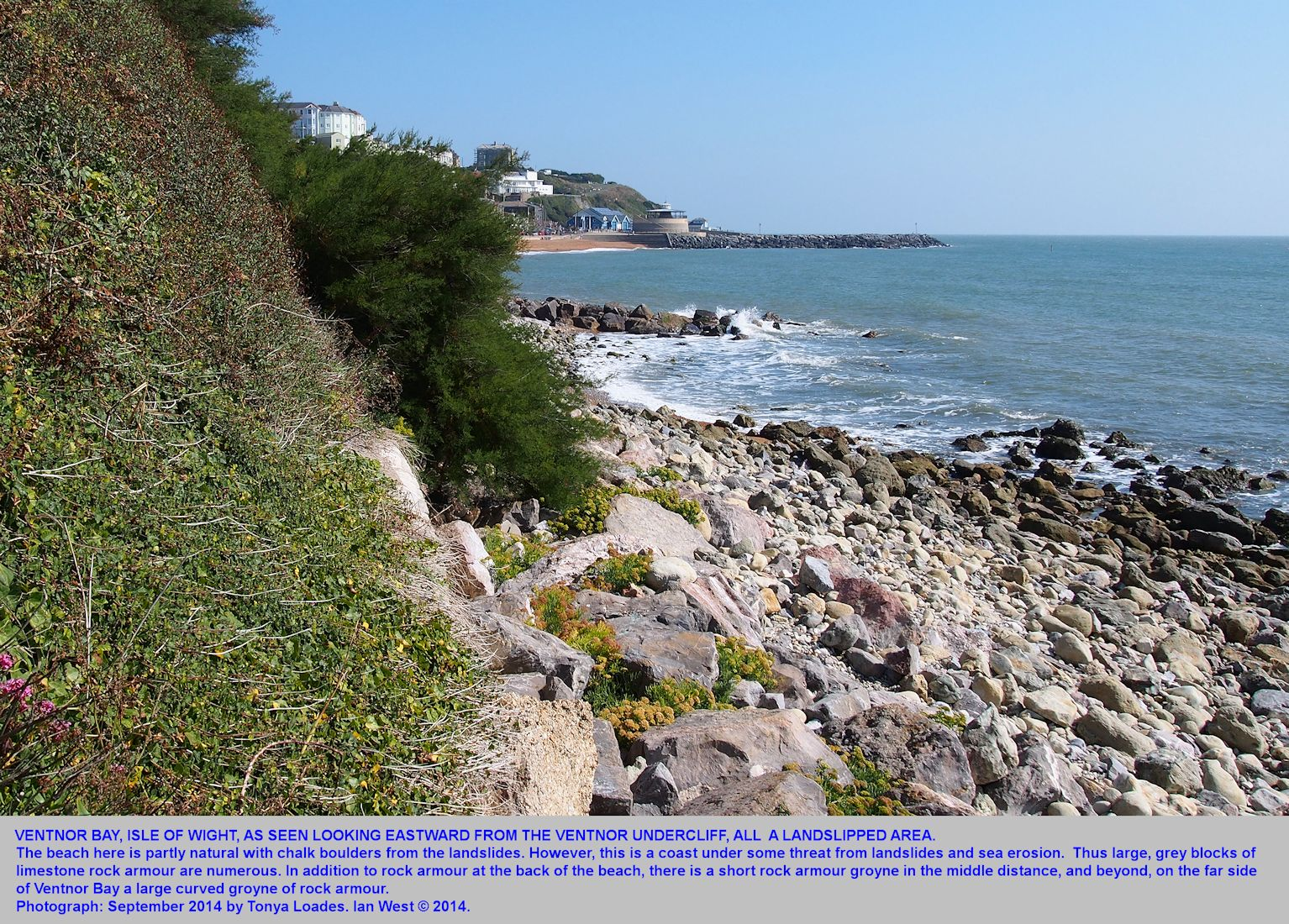 An eastward view across Ventnor Bay, Isle of Wight, with landslip rock debris in the foreground and artificial, rock armour groynes beyond