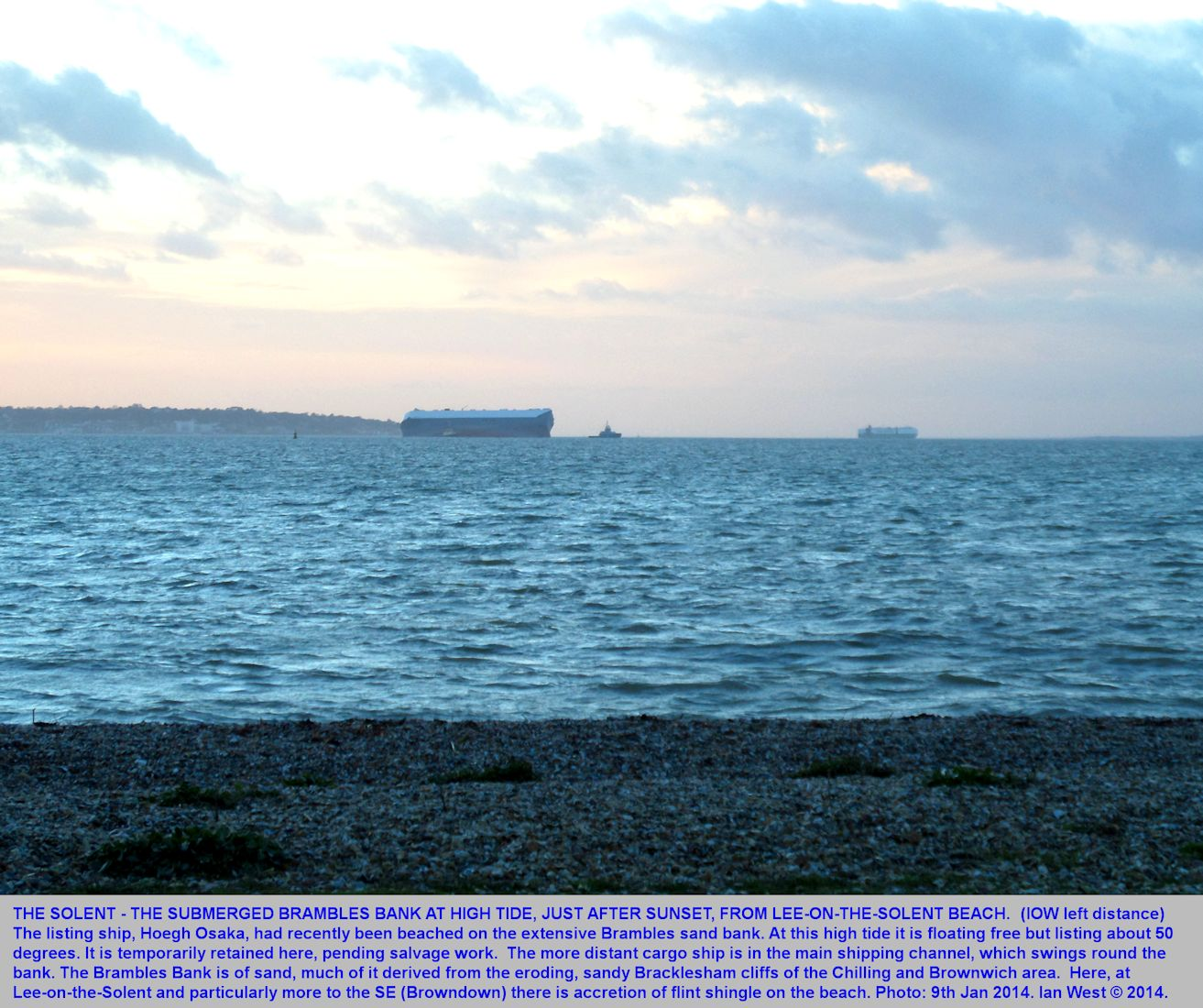 The sea area of the Brambles Bank, with the West Solent beyond, seen from the Lee-on-the-Solent beach just after sunset, with the formerly beached ship, the Hoegh Osaka, in the middle distance, and part of the Isle of Wight in the left distance